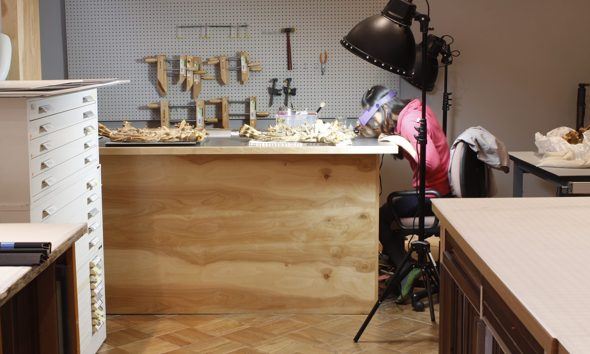 Two wall reliefs lay on a table, while Samantha works at the right under a bright light, with tools in the background.