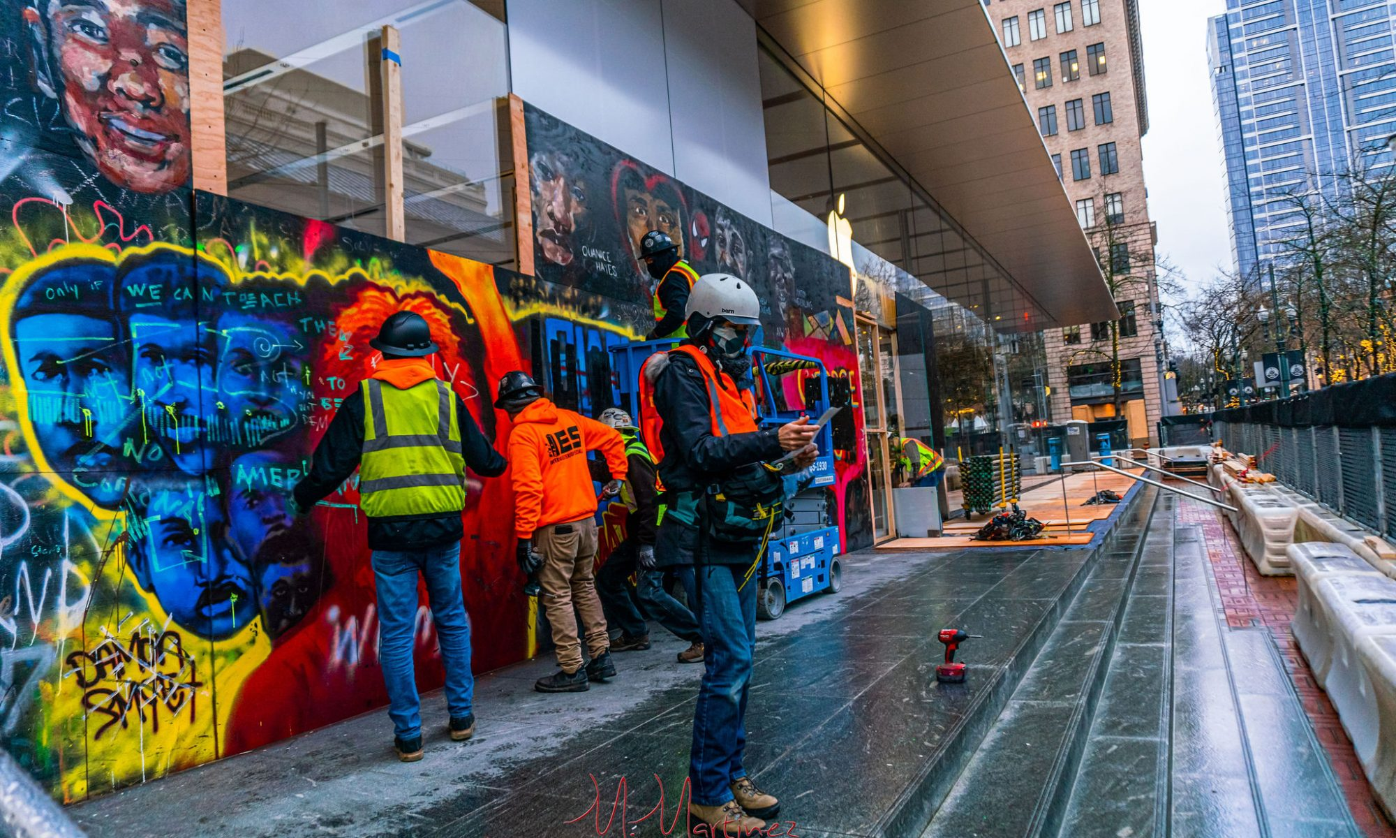Springer in safety helmet and vest organizing files while workers deinstall spraypainted George Floyd mural made at Pioneer Place Apple store